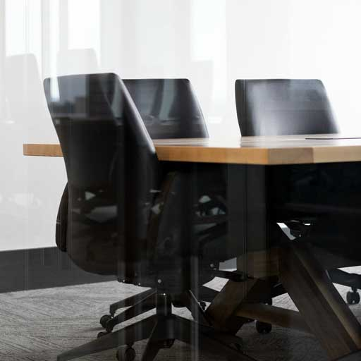 cropped photo of a conference room table with office chairs