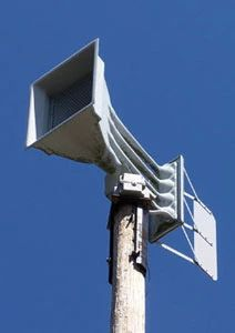 Photo of an outdoor emergency siren against a clear blue sky